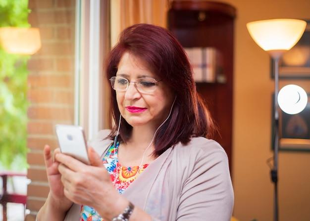 Mulher sênior usando nova tecnologia, assistindo vídeos em seu smartphone