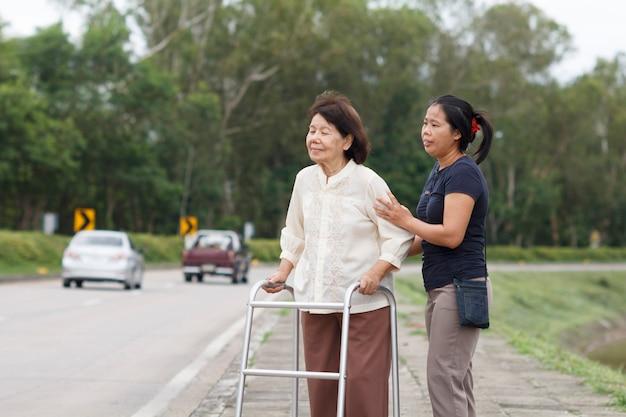 Mulher sênior usando uma rua transversal de walker.
