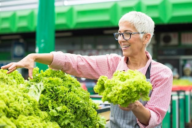 Mulher sênior vende alface no mercado