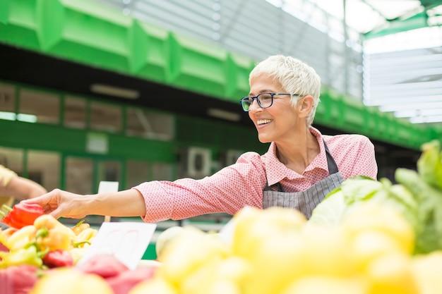 Mulher sênior vende vegetais no mercado