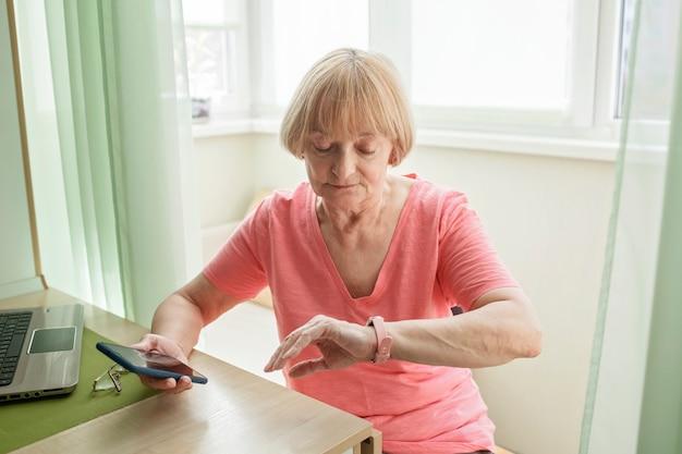 Mulher sênior verificando informações de saúde usando relógio inteligente