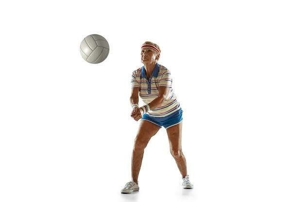 Mulher sênior, vestindo roupas esportivas, jogando vôlei em fundo branco. modelo feminino caucasiano em ótima forma permanece ativo. conceito de esporte, atividade, movimento, bem-estar, confiança. copyspace.
