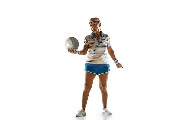 Mulher sênior, vestindo roupas esportivas, jogando vôlei em fundo branco.
