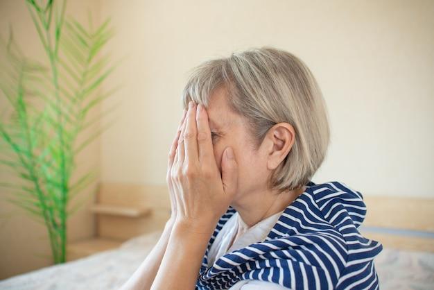 Mulher sênior viciada e alcoolismo sozinho estresse estresse sentado na cama com a cabeça entre as mãos. dor de cabeça, enxaqueca, tontura. conceitos de documentário social