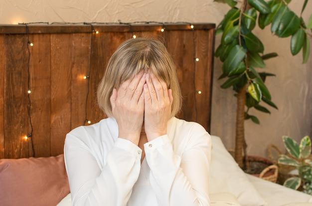 Mulher sênior viciada e alcoolismo sozinho estresse estresse sentado na cama com a cabeça entre as mãos. dor de cabeça, tontura, enxaqueca. conceitos de documentário social