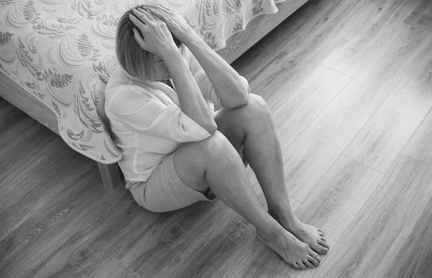 Mulher sênior viciada e alcoolismo sozinho estresse estresse sentado no chão com a cabeça entre as mãos. dor de cabeça, tontura, enxaqueca. conceitos de documentário social em preto e branco