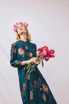 Mulher sensual atraente com coroa na cabeça e buquê de flores
