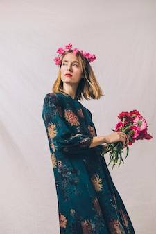 Mulher sensual com coroa de flores na cabeça e buquê de flores