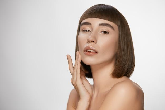 Mulher sensual com pele perfeita tocando o rosto, morena com penteado reto perfeito e ombros nus com lábios brilhantes em fundo branco
