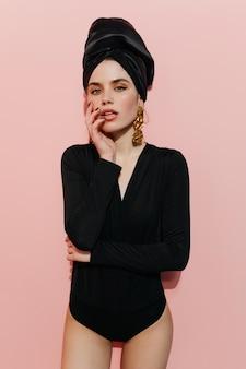 Mulher sensual com turbante preto olhando para a câmera