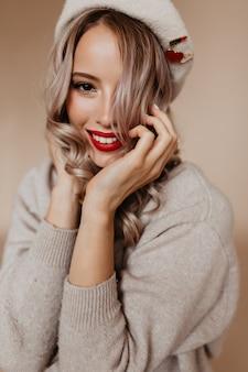 Mulher sensual e atraente em boina posando no estúdio