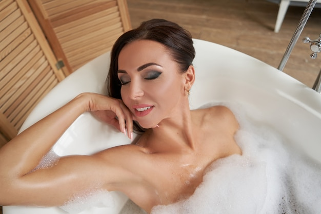 Mulher sensual e charmosa sentada na banheira com espuma no banheiro