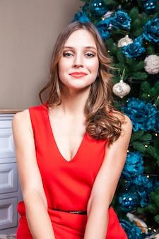 Mulher sensual e elegante em um lindo vestido vermelho e maquiagem, olhando para a câmera com paixão. tiro interno