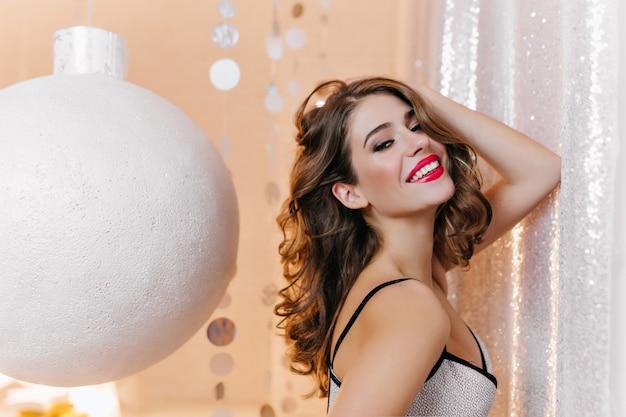 Mulher sensual e encaracolada com pele levemente bronzeada, posando antes da festa de ano novo. retrato interior da bela jovem ao lado do brinquedo de natal branco.