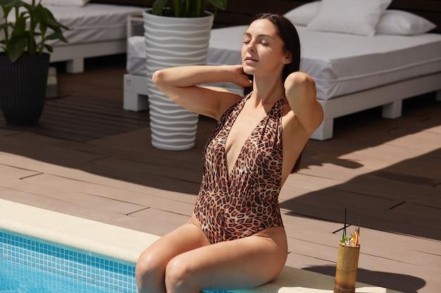 Mulher sensual e magra, sentada perto da piscina, colocando as pernas na água, toca o cabelo molhado com as mãos, vestindo roupa de banho com estampa de leopardo, descansa no resort, posando com os olhos fechados.