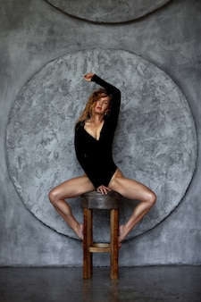 Mulher sensual e sedutora jovem ruiva com pernas sensuais no corpo posando na parede de pedra na superfície