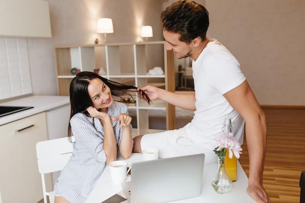 Mulher sensual em camisa azul masculina olhando com um sorriso para o namorado e apontando para a tela do laptop