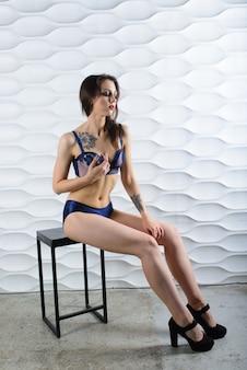Mulher sensual tatuagem na cueca azul, vermelha, rosa, branca e sapatos de salto alto no interior do estúdio.