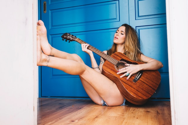 Mulher sensual tocando violão no chão