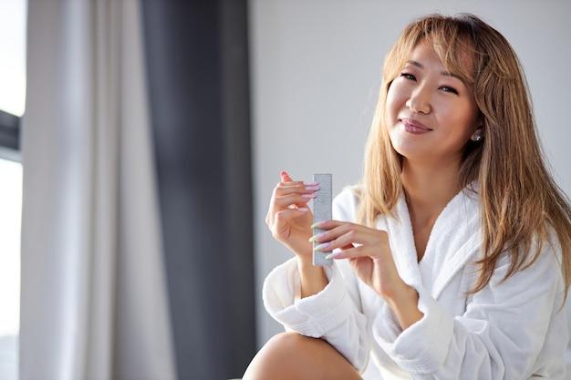 Mulher senta na cama e faz manicure, usando lixa de unha, sorriso, de roupão, em casa