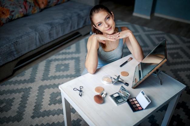 Mulher senta-se antes de espelho e sorrisos. mulher fazendo maquiagem.
