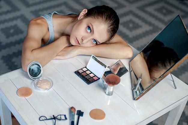Mulher senta-se antes de espelho. mulher fazendo maquiagem