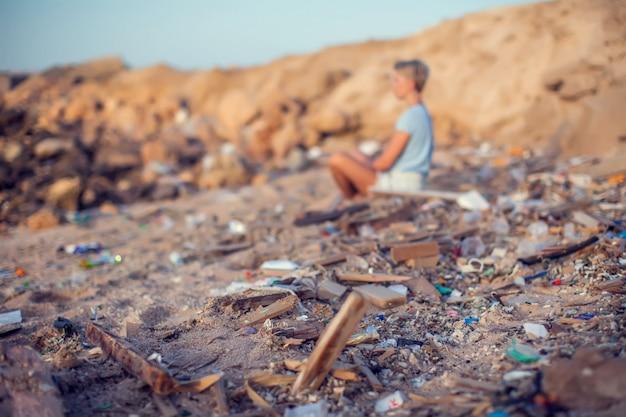 Mulher senta-se na praia entre o lixo. conceito de poluição ambiental