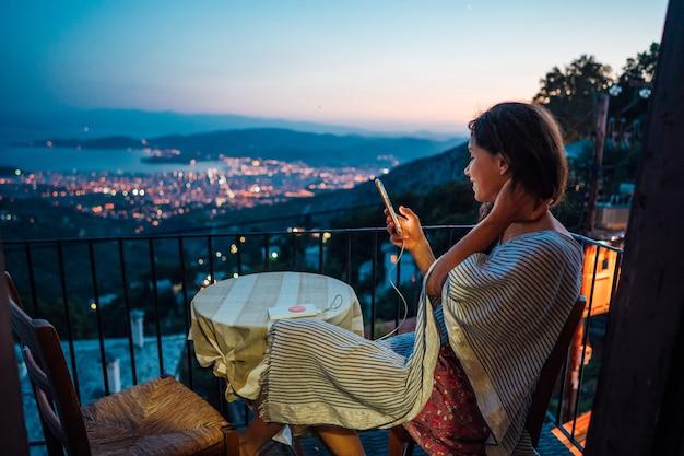 Mulher senta-se na varanda, no fundo a cidade à noite