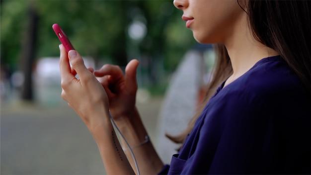 Mulher senta-se no banco e usando o smartphone. fechar vista