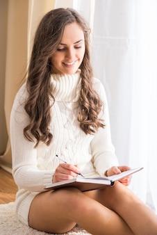 Mulher senta-se no chão com o livro em casa.