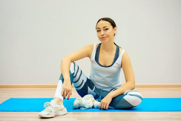 Mulher senta-se no tapete azul cansado após o treino, em roupas esportivas em casa