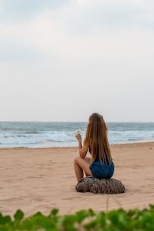Mulher senta-se pelo oceano