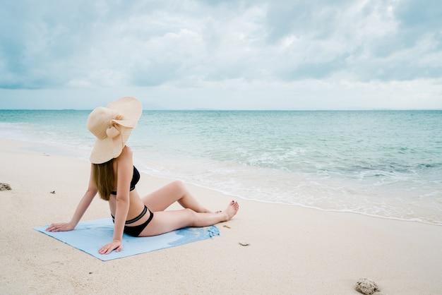 Mulher sentada à beira-mar vestir um biquíni usando um chapéu de mar.