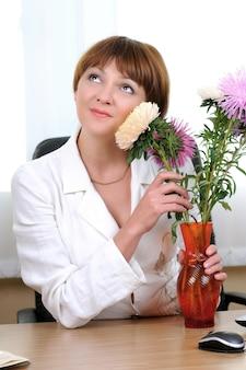 Mulher sentada à mesa abraçando um buquê de flores