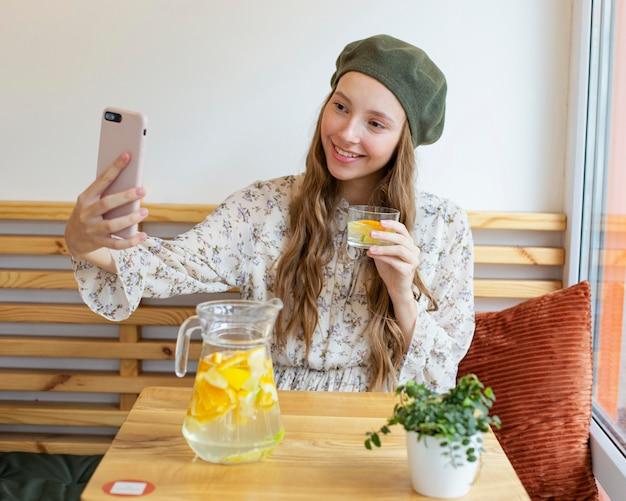 Mulher sentada à mesa com um tiro no meio, segurando um copo de limonada e tirando uma selfie