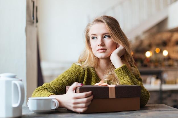 Mulher sentada à mesa com uma caixa de presente e esperando por alguém