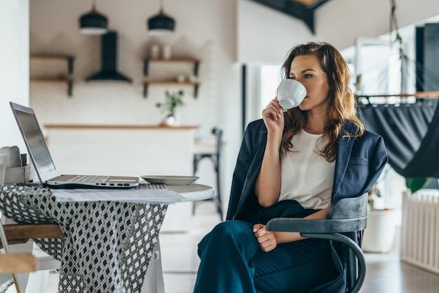 Mulher sentada à mesa da cozinha com laptop, bebendo de uma caneca.