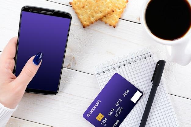 Mulher sentada à mesa e paga a compra no smartphone
