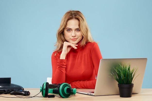 Mulher sentada à mesa em frente a um controlador de fones de ouvido de laptop jogando online