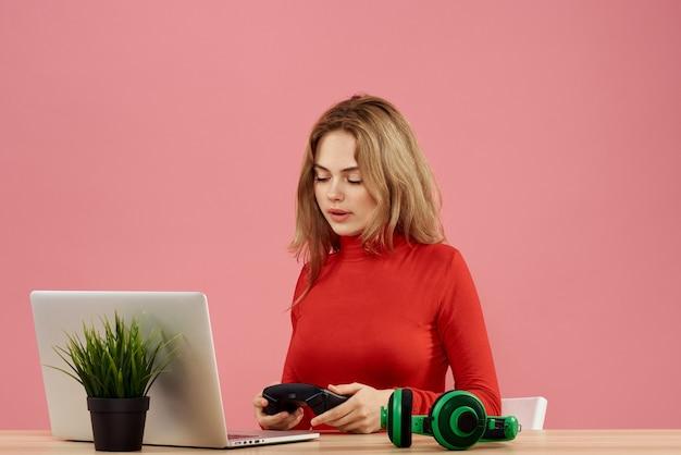 Mulher sentada à mesa em frente a um laptop com um gamepad nas mãos, jogando fones de ouvido de tecnologia