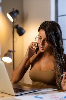 Mulher sentada à mesa falando ao telefone