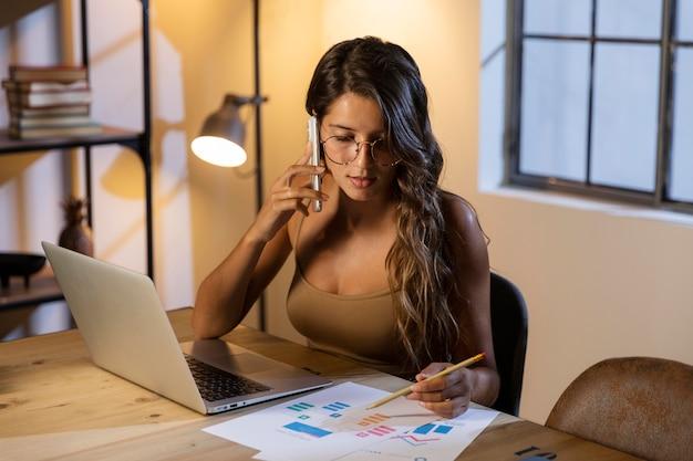 Mulher sentada à mesa falando no telefone e olhando papéis