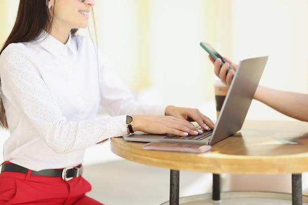 Mulher sentada à mesa no bar com um amigo e digitando no close do teclado do laptop. conceito de site de reuniões