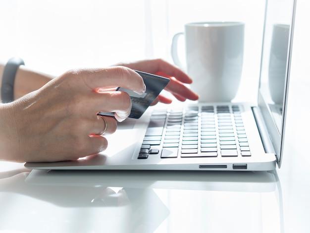 Mulher sentada à mesa, tomando chá e olhando para um laptop, paga por compras
