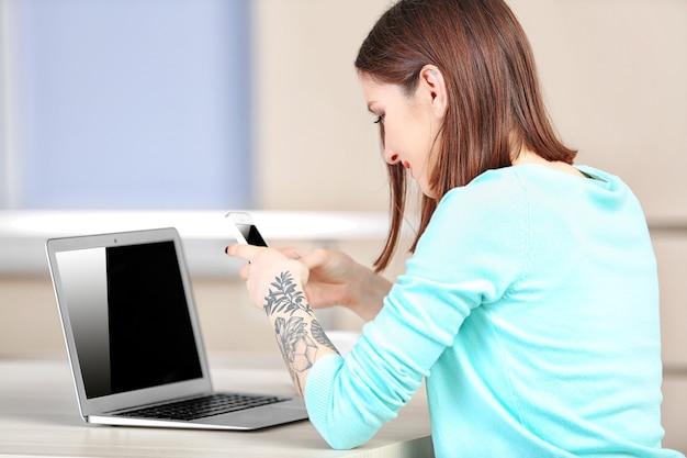 Mulher sentada à mesa trabalhando com um laptop