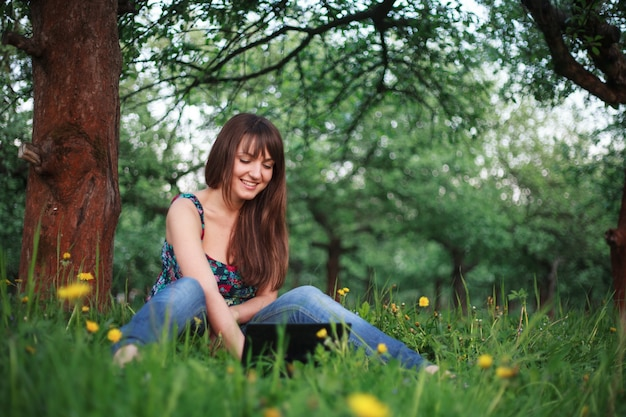 Mulher sentada ao ar livre com netbook e sorrindo. rede social