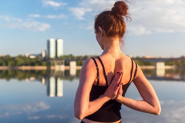 Mulher sentada ao ar livre, meditando em posição de ioga perto do rio.