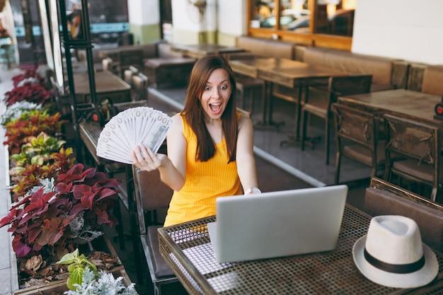 Mulher sentada ao ar livre na rua, café, café, sentada com um computador laptop moderno, segurando um monte de notas de dólares