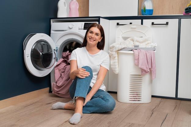 Mulher sentada ao lado da máquina de lavar com uma cesta cheia de roupas