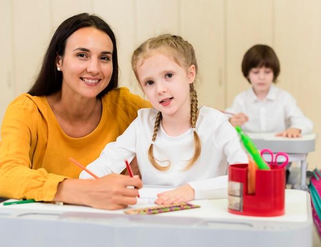 Mulher sentada ao lado de seu aluno